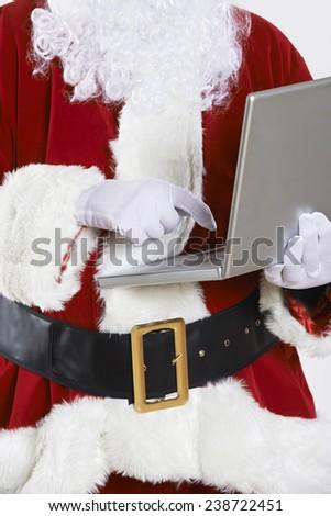 Santa Claus Using Laptop On White Background - stock photo