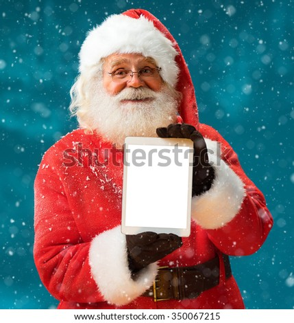 Santa Claus using tablet computer / Merry Christmas & New Year's Eve concept / Closeup on blurred blue background. - stock photo