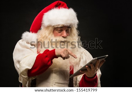 Santa Claus using tablet computer to surf internet and communicate in social media with children - stock photo