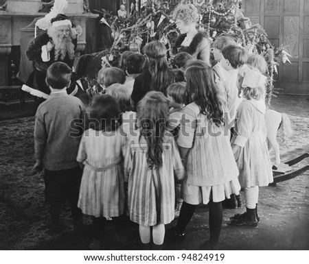 Santa Claus visiting with large group of children - stock photo