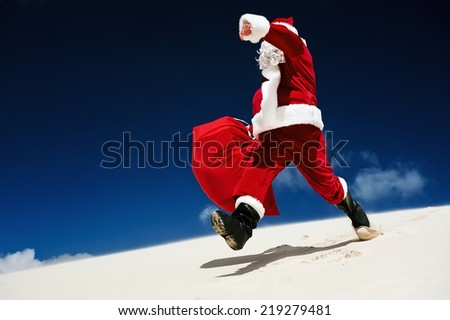 Santa Claus walking down a sand dune on a beach - stock photo