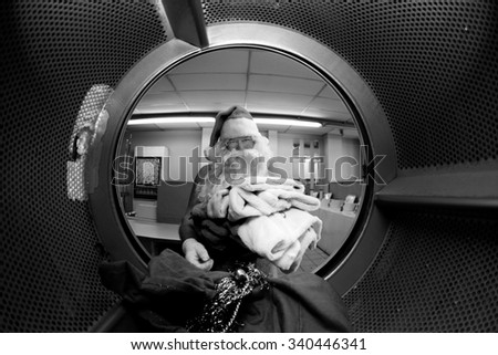 Santa Claus washes his own clothes at the Laundromat before Christmas. Focus on Santa's Clothes. Shot with a Fish eye Lens from the Inside out for a Unique and Funny View unseen by anyone until now. - stock photo
