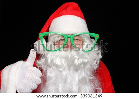 Santa Claus wears Giant Green Glasses while he poses for photos in a Photo Booth. Santa Claus humor. Santa Claus Joking around. Christmas Humor. Funny photo. Funny image. Laughing Santa. - stock photo
