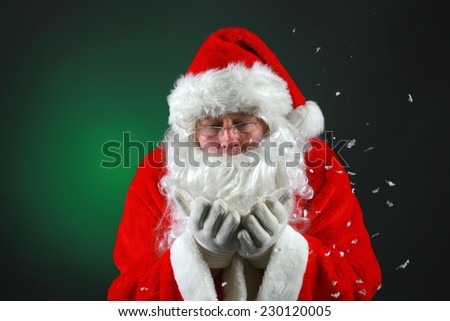 Santa Claus wears his eye glasses and blows snow while looking into the camera. Santa Claus loves Christmas and Snow and all things magical.  Christmas is a Magical Time of the year. - stock photo