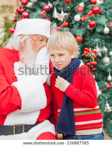 Santa Claus whispering in boy's ear in front of Christmas tree - stock photo