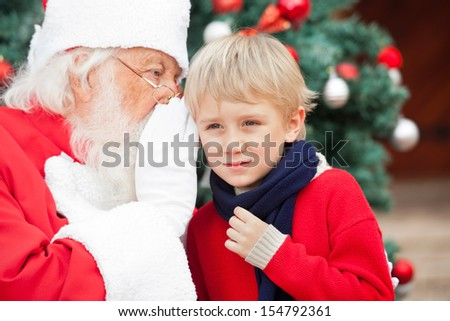 Santa Claus whispering in boy's ear outdoors - stock photo