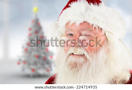 Santa claus winking against blurry christmas tree in room