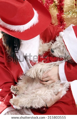 Santa claus with a white puppy in his arms. - stock photo