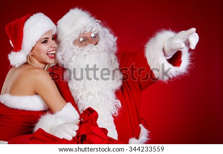 Santa Claus with a woman Christmas helper - stock photo