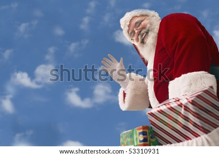 Santa Claus with bag of presents waves against a background of Cumulus clouds in an azure blue sky - stock photo