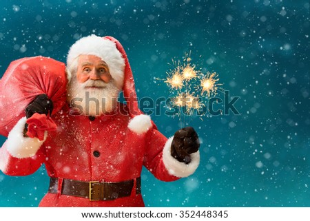 Santa Claus with big bag of gifts and Bengal lights and looking at camera / Merry Christmas & New Year's Eve concept / Closeup on blurred blue background. - stock photo