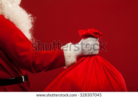 santa claus with big bag on shoulder glasses on red background - stock photo