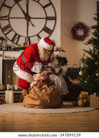 Santa Claus with Child at Home. Presenting Christmas Gifts from his Sack - stock photo