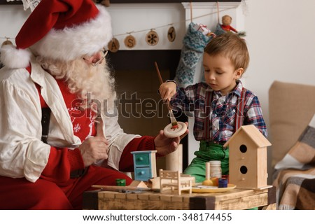 Santa Claus with Child making Christmas Gifts and Toys at Home - stock photo