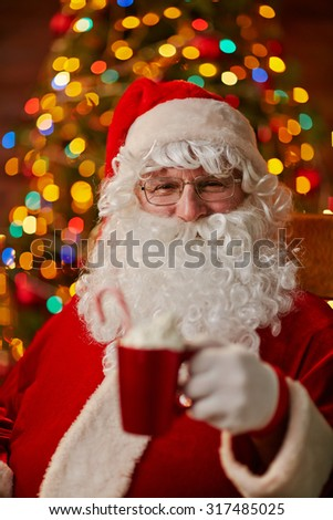 Santa Claus with cup of latte looking at camera - stock photo