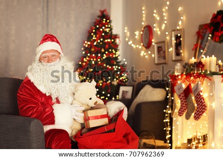Santa Claus with gift bag in room decorated for Christmas