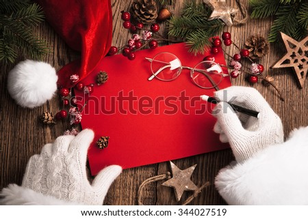 Santa Claus with gifts and red card on wooden table - stock photo