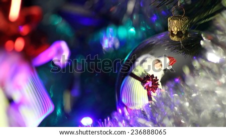 Santa Claus with gifts in reflection Christmas ball