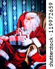Santa Claus with gifts sitting in a comfortable chair near the fireplace at home. - stock photo