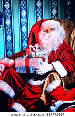 Santa Claus with gifts sitting in a comfortable chair near the fireplace at home.