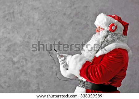 Santa Claus with headphones listening to music on gray wall background - stock photo