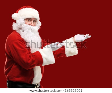 Santa Claus with his arms out in a presenting gesture. Isolated design element - stock photo