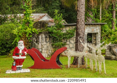 Santa Claus with his sleigh waiting for five more reindeer to join them so they can begin delivering gifts for Christmas - stock photo