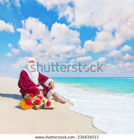 Santa Claus with many golden gifts relaxing on tropical beach  - christmas  or happy new year in hot countries concept