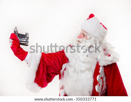 Santa Claus with old camera on the white background. Isolated - stock photo