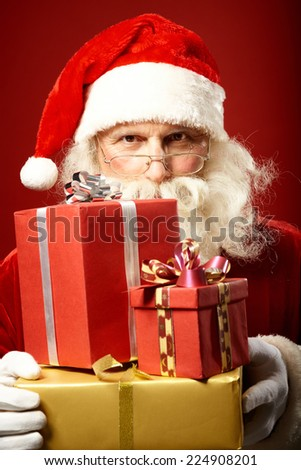Santa Claus with pile of gifts looking at camera over eyeglasses - stock photo