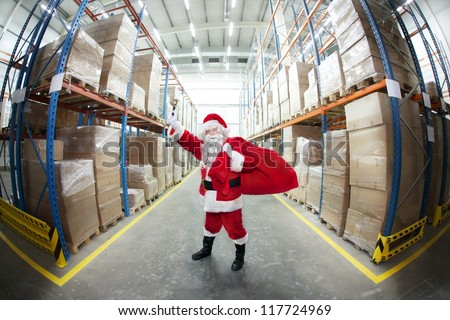 Santa Claus with red sack , ringing in a bell in storehouse full of  gifts - stock photo
