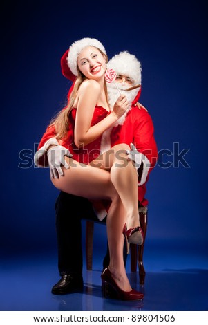 Santa Claus with sexy girl in Santa hat. - stock photo