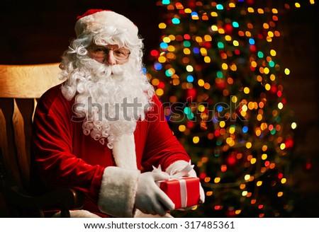 Santa Claus with small giftbox looking at camera - stock photo