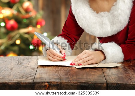 santa claus woman and pen - stock photo