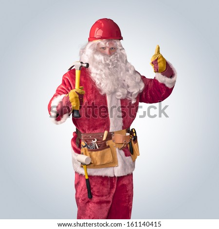 Santa Claus worker in helmet with hammer on an isolated background - stock photo