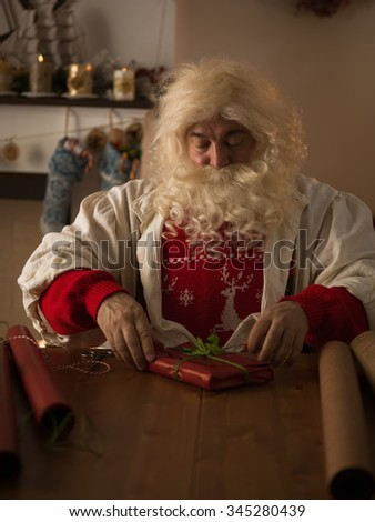 Santa Claus Working at Home. Wrapping Gifts for Children - stock photo