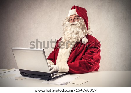 Santa Claus working with the computer - stock photo
