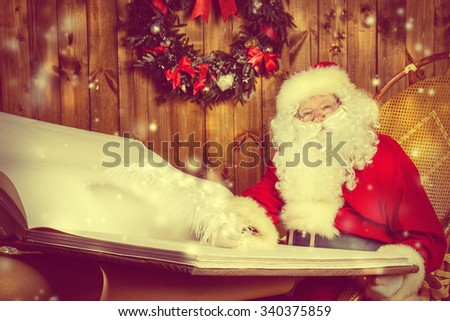Santa Claus writing a magic book in his wooden house. The magic of Christmas. - stock photo