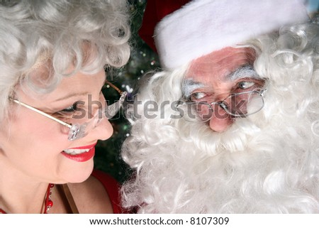 Santa clause and his wife sharing a look of love - stock photo