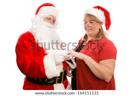 Santa Clause giving his wife a beautiful diamond ring for Christmas.  Isolated on white.   - stock photo