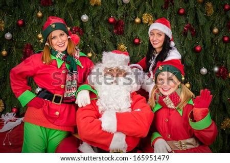Santa Clause with elf helper woman Christmas decor - stock photo
