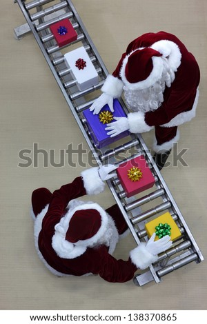 Santa clauses working at production line in presents factory - stock photo