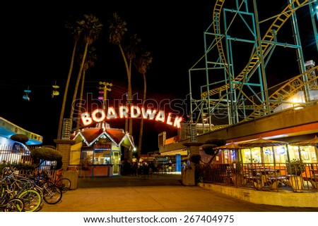 SANTA CRUZ, CA-AUG 2, 2014: Night view of the Santa Cruz Beach Boardwalk, seen  from the front entry with its bright neon sign. The vintage seaside amusement park first opened in 1907.  - stock photo