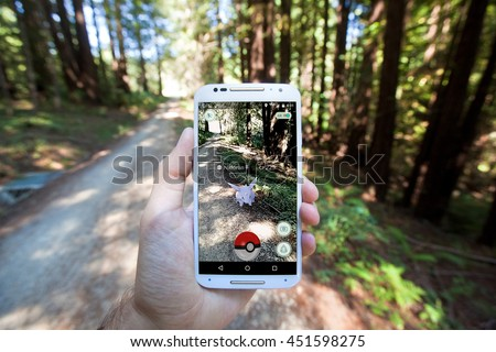 "SANTA CRUZ, CALIFORNIA - JULY 12, 2016: The hit augmented reality smartphone app ""Pokemon GO"" shows a Pokemon encounter overlain on a real world trail in the forest."
