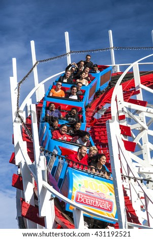SANTA CRUZ, CALIFORNIA, USA-NOVEMBER 15, 2014 : People on Giant Dipper the fifth oldest wooden coaster in the US. Built by Arthur Looff in 1924 and maximum speed is up to 46 mph. Taken in Santa Cruz. - stock photo