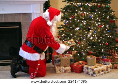 Santa delivering presents under the tree. - stock photo