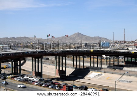 Santa Fe bridge across the Rio Grande (Rio Bravo) river is a major crossing point and smuggling route between El Paso, USA (to the right) and Ciudad Juarez, Mexico (to the left). - stock photo