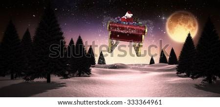 Santa flying his sleigh against full moon over snowy landscape - stock photo