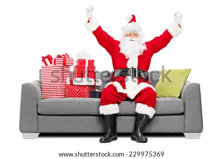 Santa gesturing happiness seated on sofa with gifts isolated on white background - stock photo
