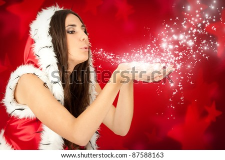 santa girl blowing snow from her hand on red background - stock photo